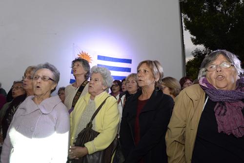 Mujeres entonando el himno con la bandera nacional al costado