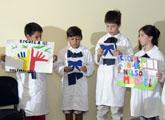 Niños de túnica y moña recitando frases de Mandela